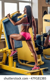Suntanned fitness female doing workouts on legs exercising machine in a gym.