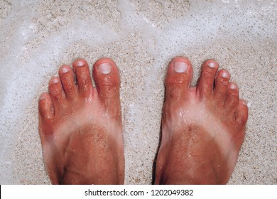 suntanned human feet with stripes of white skin from sandals in summer standing on the sand and sea waves
