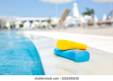 Sun-tanning cream by a blue swimming pool on a beautiful sunny day