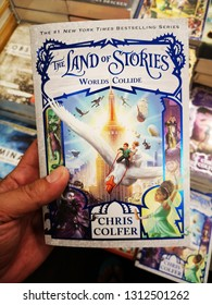 Sunway Piramid, Malaysia - 9 February 2019 : Hand hold a THE LAND OF STORIES - Worlds Collide by CHRIS COLFER for sell in the book stores.