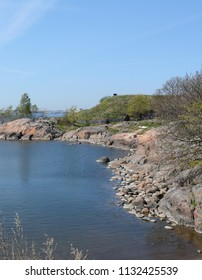Suomenlinna beach and rocky cove on a sunny day in Finland. Trees and shrubs coming into leaf in spring.