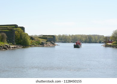 SUOMENLINNA, FINLAND - May 14, 2018: Red and black boat navigates the waters through the Suomenlinna fortress islands