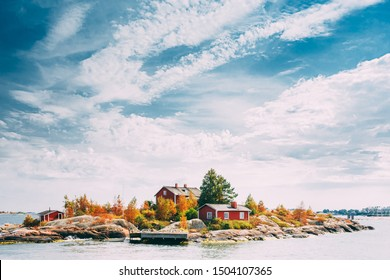 Suomi Or Finland. Beautiful Red Finnish Wooden Log Cabin House On Rocky Island Coast In Summer Sunny Evening. Lake Or River Landscape. Tiny Rocky Island Near Helsinki, Finland.