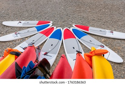 Sup board and kayaks rental place on the beach. Surfboards, many different surf boards on the beach, water sport, happy active summer vacation. Row of stand up paddle boards ready to rent.