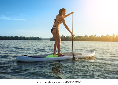 SUP confident woman swimsuit standing with a paddle on the surfboard