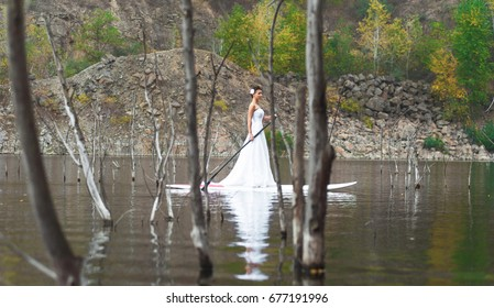 SUP the girl in a white dress with a paddle board floats on the river
