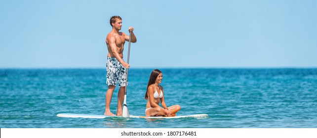 SUP Inflatable paddle board man athlete paddleboarding with woman on paddleboard. Fun summer watersport sport for couples on vacation. Panoramic banner.