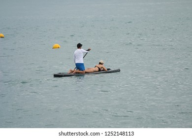 Sup Paddle in Ilhabela, Brazil. Man paddling on the table and woman enjoying the trip.