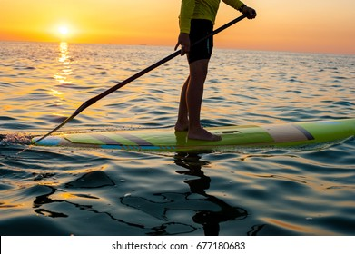 SUP silhouette of athletic man standing with a paddle on the surfboard at sunset stand up paddle boarding, legs