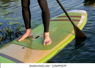 SUP silhouette of young girl paddle boarding at sunset