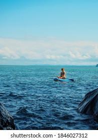 SUP Stand up paddle board. Romantic girl on paddle board in the sea near stone beach. Blue sea Mtsvane Kontskhi Beach, Batumi, Georgia.