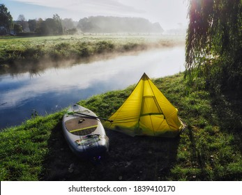 SUP (Stand up paddling) board next to a small tent at river Ilmenau on a camp site in Wichmannsburg, Germany (camping with SUP)