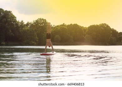 SUP yoga at stand up paddling handstand