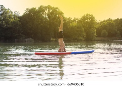 SUP yoga at  stand up paddling headstand