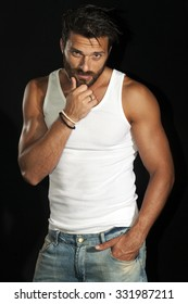 Super athlete, handsome man in white t shirt with muscular body in jeans