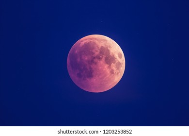 Super Bloody Moon, beginning of full eclipse phase against blue starry sky background