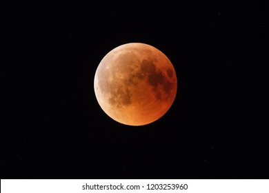 Super Bloody Moon, beginning of full eclipse end phase against starry sky background