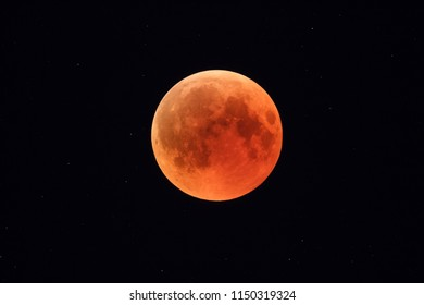 Super Bloody Moon, full eclipse phase against starry sky background