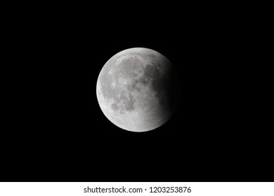 Super Bloody Moon, full eclipse last phase against black sky background, small part of Moon surface covered by Earth's shadow
