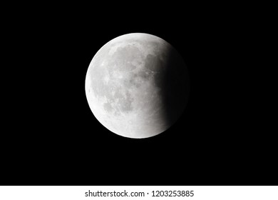 Super Bloody Moon, full eclipse last phase against black sky background, quarter of the Moon surface covered by Earth's shadow