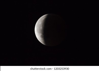 Super Bloody Moon, full eclipse end phase against black sky background, three-quarters of the Moon surface covered by Earth's shadow