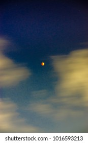 Super Blue Blood Moon in the sky with many clouds moving pass. Super Blue Blood Moon is a blue moon, a supermoon, and a blood moon ( a lunar eclipse) are happening around the same time