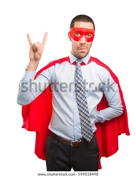 Super businessman doing a rock gesture