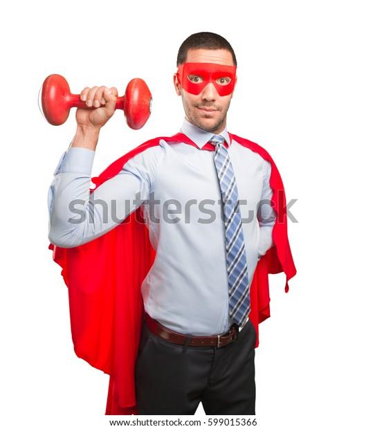 Super businessman holding a dumbbell