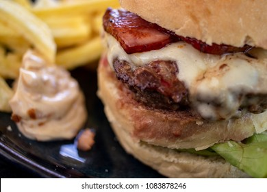 Super close up of bacon cheese burger with sauce and french fries in a restaurant