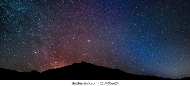 Super colorful panoramic landscape of night sky with dark mountains at foreground.