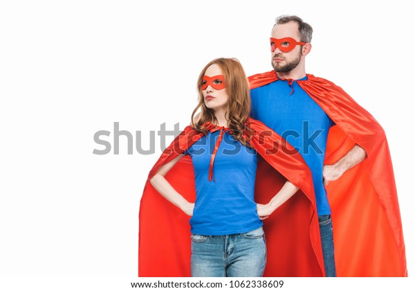 super couple in masks and cloaks standing with hands on waist and looking away isolated on white