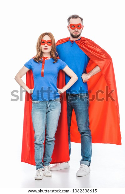 super couple in masks and cloaks standing with hands on waist and looking at camera isolated on white