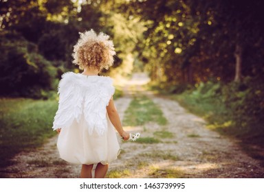 Super cute anonymous blonde curly hair girl child wearing white dress and angel wings, walking on countryside road. Backside view. Concept of child angel.