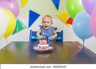 Super cute baby blowing her first birthday candle