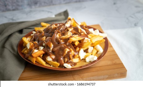 Super delicious Poutine with French fries onion gravy and mozzarella cheese curds on top.