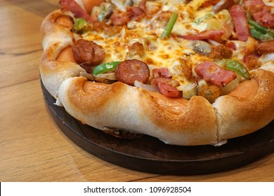 Super deluxe pizza on wooden tray medium size, On wooden table, Traditional Italian fast food