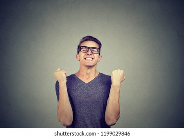 Super excited young man in glasses holding fists in celebration of success on gray background