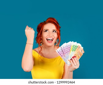 Super excited young woman holding bunch of Euro banknotes, clinching fists, celebrating winning lottery. Ecstatic woman holding lots of money. Caucasian person in yellow dress redhead isolated on blue