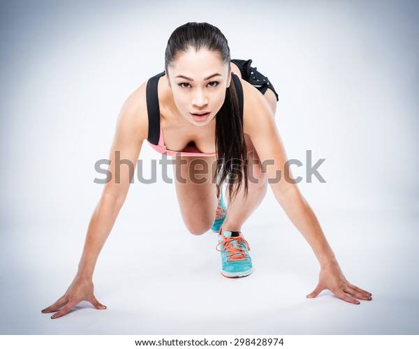 Super fit girl in running pose looking to camera ready for anything.