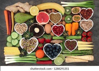 Super food concept for a healthy diet with fruit and vegetables, dairy, spices, nuts, legumes, cereals and grains, high in antioxidants, anthocyanins, dietary fibre and vitamins.