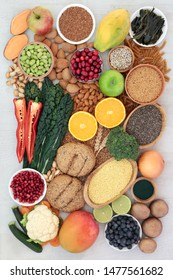 Super food concept for a high fibre vegan diet with fruit, vegetables, whole grain rolls, whole wheat pasta, nuts,  grains, seeds and spirulina powder. High in antioxidants, anthocyanins & vitamins.