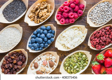 Super food, fruits, berries, nuts, seeds top view on rustic wood background. Detox, superfood concept.
