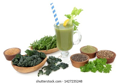 Super food health drink with vegetables, wheat grass powder, chia, flax and hemp seeds. Health foods high in antioxidants, vitamins, minerals, dietary fibre. On white background with copy space.