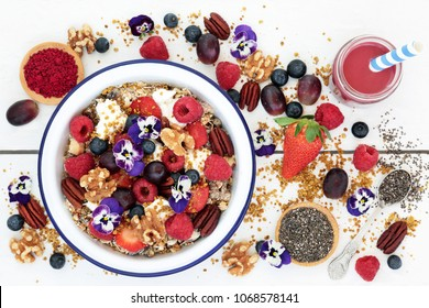 Super food healthy breakfast concept with viola flowers, acai berry smoothie and powder, fruit, granola, yoghurt, nuts, chia seed and pollen grain, high in protein, omega 3, antioxidants & vitamins.