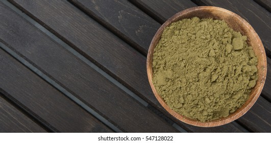 Super food hemp powder in a bowl over wooden background