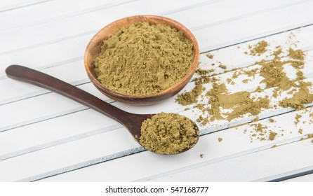 Super food hemp powder in a spoon over wooden background