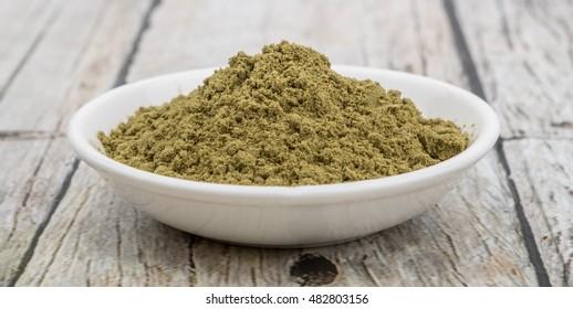Super food hemp powder in white bowl over wooden background