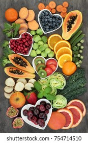 Super food for a high fiber diet with fresh fruit and vegetables, concept of foods high in smart carbohydrates, antioxidants and vitamins, on marble background, top view.
