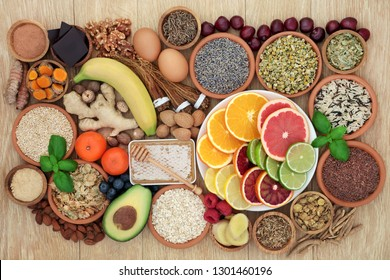 Super food to relieve anxiety and stress with herbs and spices used in herbal medicine that also help with relaxation and reduce chronic fatigue and depression. Top view on oak wood table.