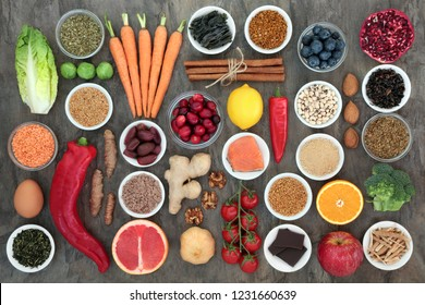 Super food to slow the ageing process concept with fish, fruit, vegetables, seeds, nuts, herbs, spices, supplement powders, green and black teas, high in antioxidants, dietary fibre and vitamins.